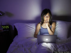 Woman working late on laptop in bed