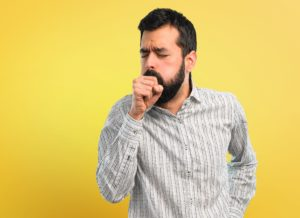 man with beard is suffering with cough and feeling bad